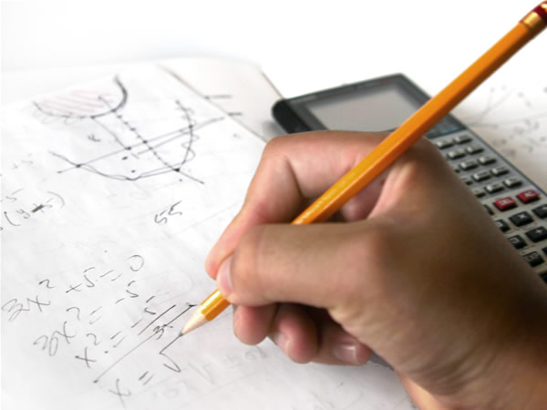 A person's hand doing mathemtics problem on paper with a pencil and a calculator